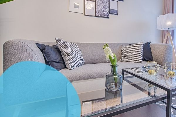 Image depicts a light grey sofa in a living room.